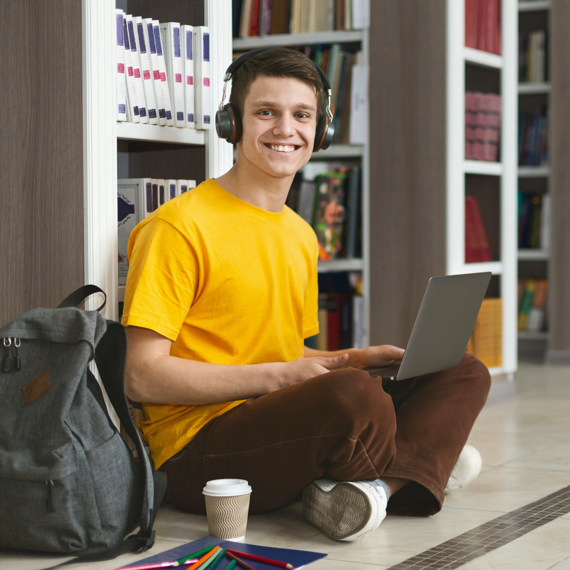 Portrait of cheerful student working on new project at library